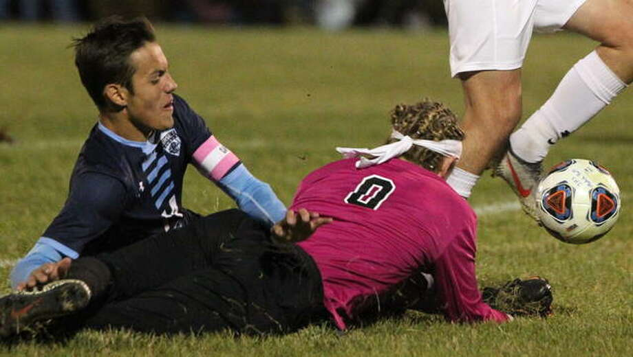 Ethan Snider of Jersey, left, collides with Jacksonville goalie Tyler Pool in the first half of Tuesday night's Jacksonville Class 2A Regional semifinal game. Snider received a yellow card after the play and received a second later, resulting in a player advantage for Jacksonville. Jersey, however, grabbed a 2-0 victory. Photo: Dennis Mathes, Journal-Courier | For The Telegraph