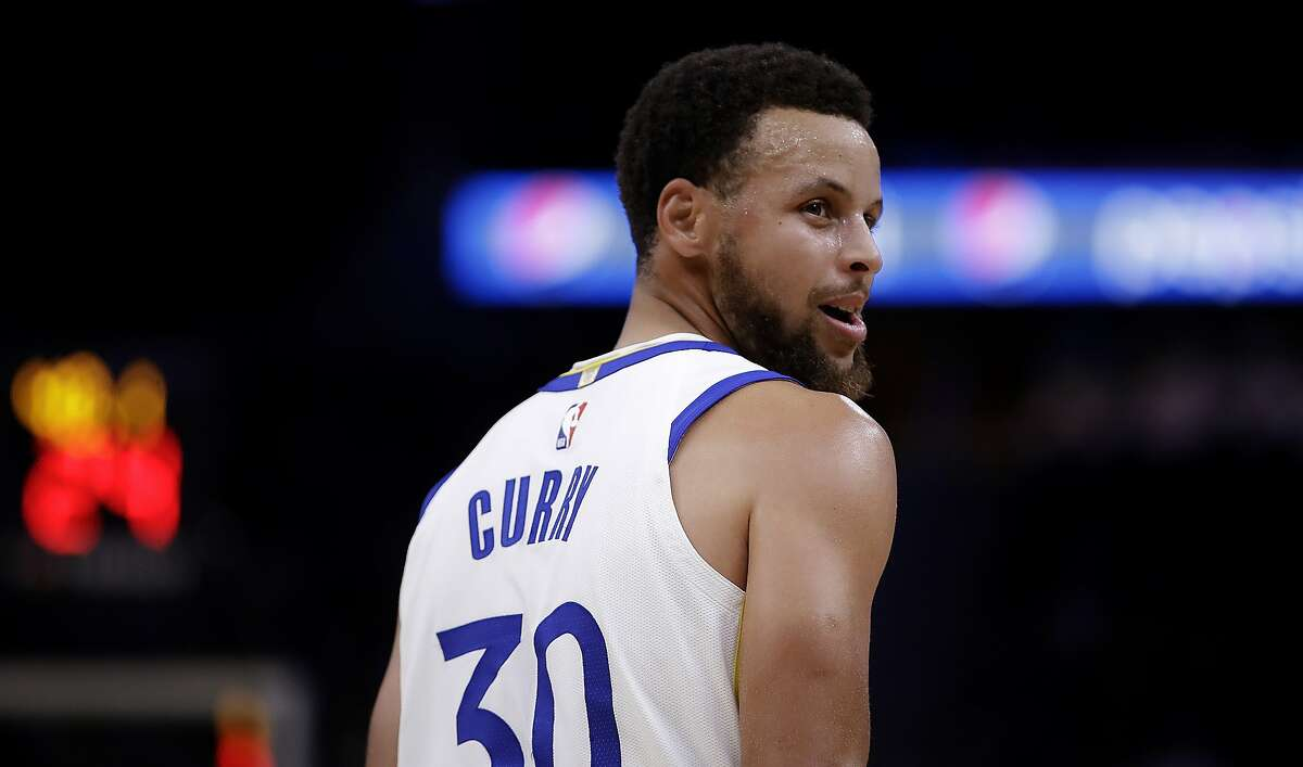 Golden State Warriors' Stephen Curry looks at the Los Angeles Lakers' bench during the first half of a preseason NBA basketball game Friday, Oct. 18, 2019, in San Francisco. (AP Photo/Ben Margot)