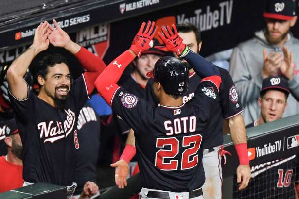Washington Nationals third baseman Anthony Rendon (6) ( left) and the Washington Nationals dugout congratulates Washington Nationals left fielder Juan Soto (22) after a home run in the sixth inning during Game 1 of the World Series between the Washington Nationals and the Houston Astros at Minute Maid Park on Oct. 22, 2019.