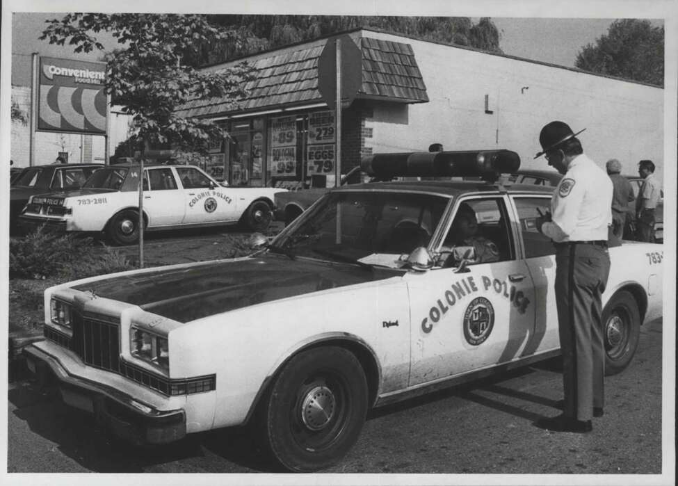 Convenient Food Mart, corner of Myers Drive and Sand Creek Road, Colonie, New York - Deputy Chief Edward R. Frank of Colonie Police Department talks to police officer in squad car, October 23, 1984 (Bob Richey/Times Union Archive). Keep clicking for more photos that show what Albany police cars looked like through the years.