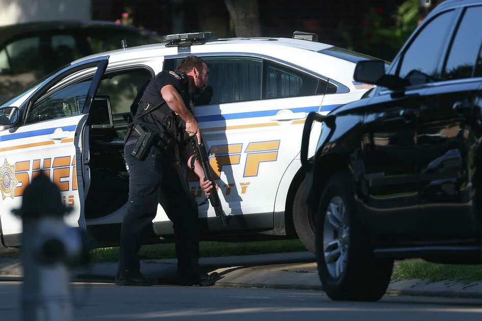 Harris County Sheriff's deputies work a scene where an armed suspect is barricaded inside his home in the 6900 block of Hamilton Falls Drive on Wednesday, Oct. 23, in Spring.