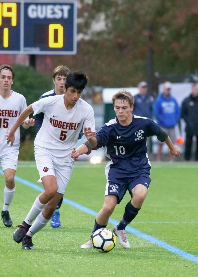 Wilton's Connor Uitterdijk (right) vies for the ball with Ridgefield's Ludwin Godoy during Tuesday's 1-1 tie. Photo: Gretchen McMahon / For Hearst Connecticut Media
