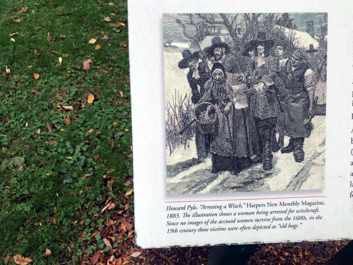 An illustration of a woman being arrested for witchcraft adorns a sign in front of what was once called Edward's Pond. Taken Oct. 16, 2019 in Fairfield, Conn.