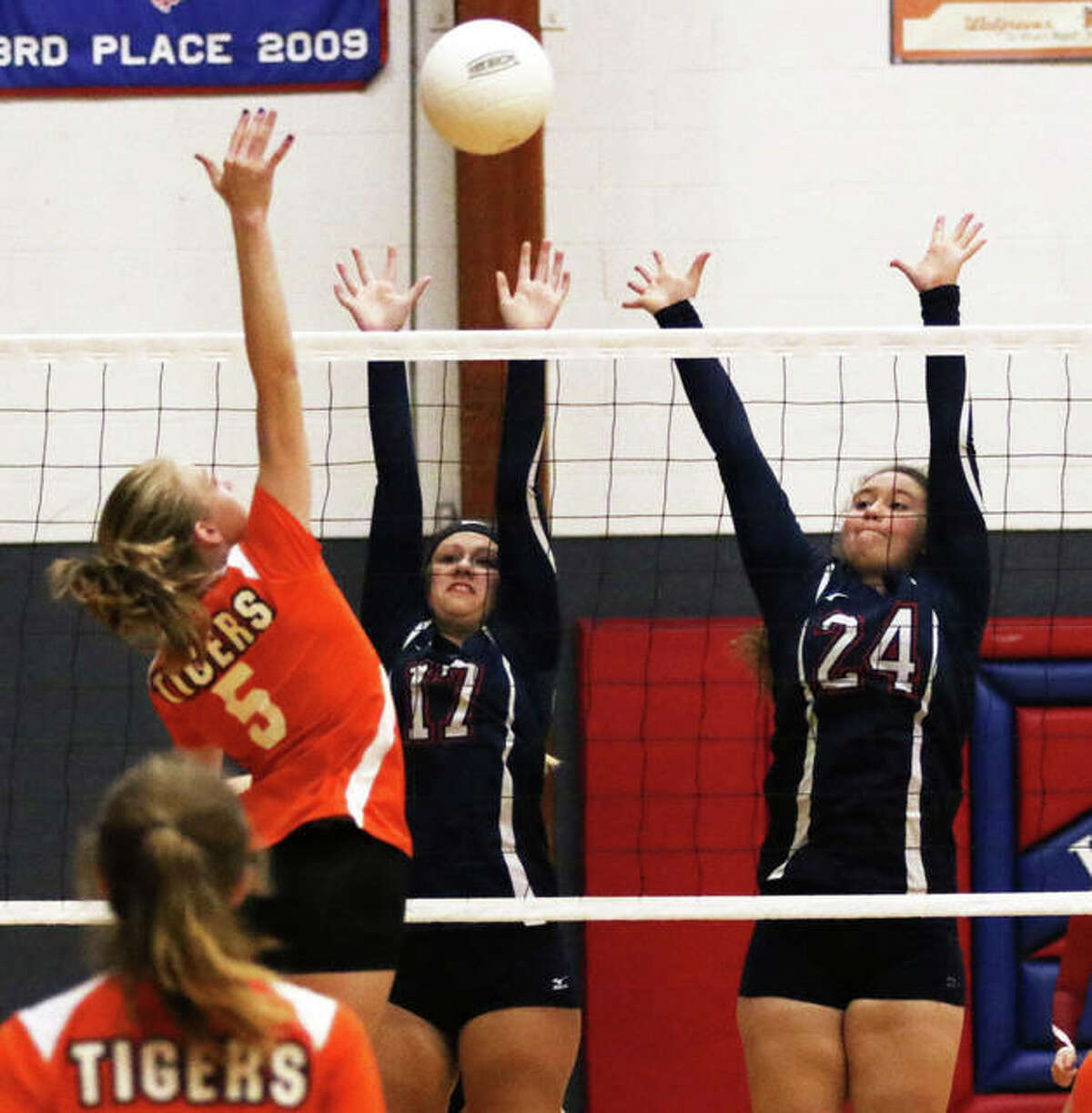 Carlinville's Kelsey McKee (17) and Haley Wills (24) put up a block while Greenfield's Alexis Pohlman attacks during an Oct. 5 match at the Carlinville Tourney. Both the Cavaliers and Tigers posted victories Tuesday night.
