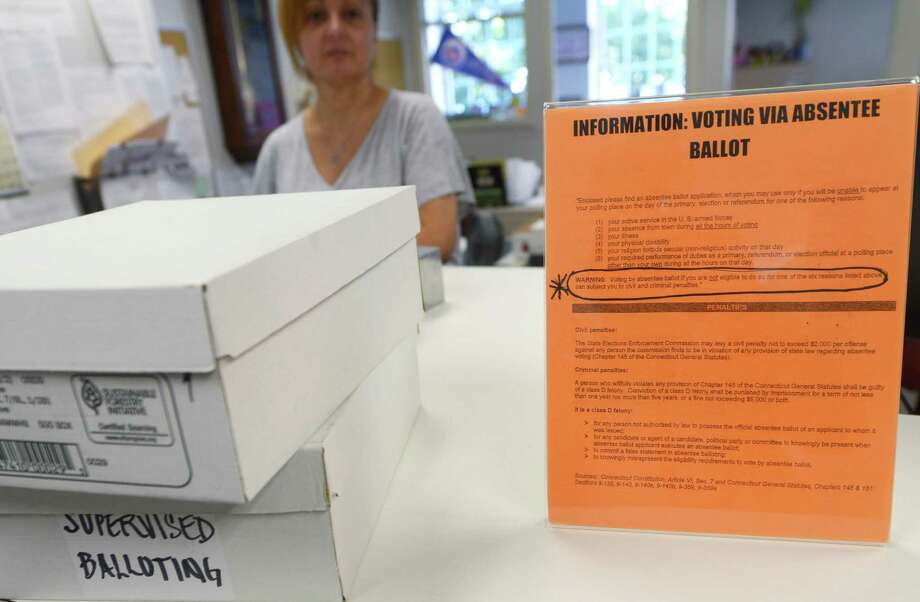 A notice detailing the penalties for illegitimately casting an absentee ballot sits on the counter of the Town Clerk's office in Norwalk last year. Photo: Erik Trautmann / Hearst Connecticut Media / Norwalk Hour
