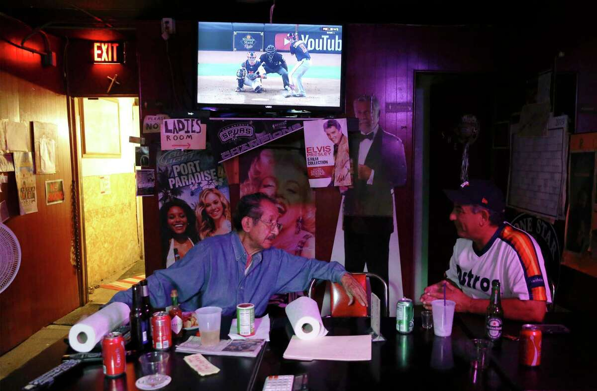 Tony Lopez of Tony's Bar on Brooklyn Avenue (left) chats with long-time patron JR Moreno while watching Game 1 of the 2019 World Series on Tuesday. Express-News)