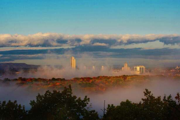 Fog settles around the buildings in Albany as the sunrises on Wednesday, Oct. 23, 2019, in a view from Rensselaer, N.Y. (Paul Buckowski/Times Union)