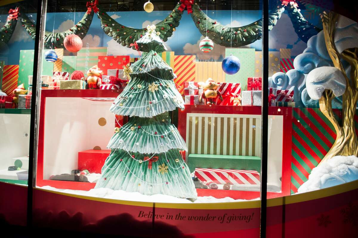 Visitors watch the adoptable puppies and kittens at the Macy's windows in San Francisco in 2018.