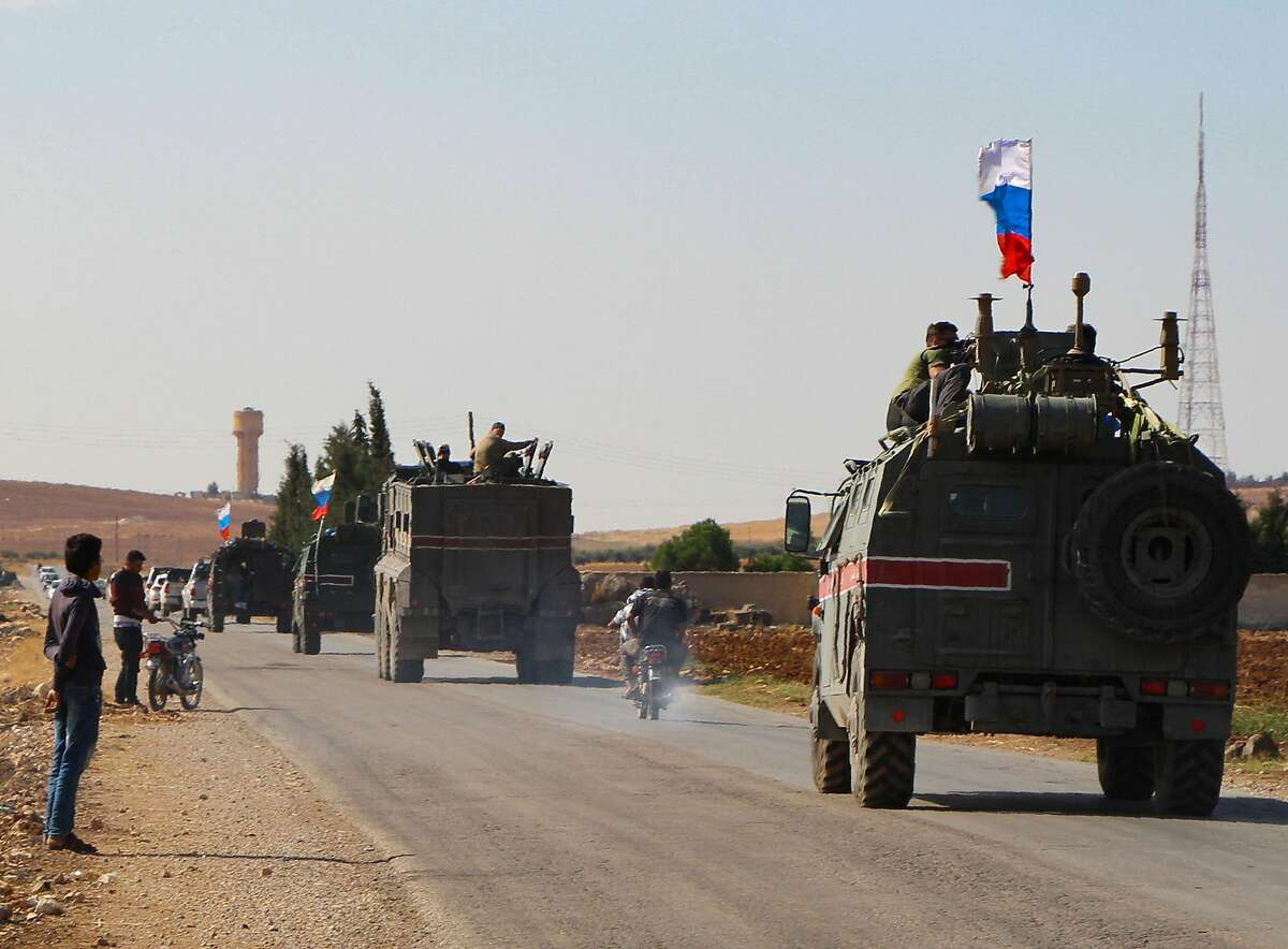 TOPSHOT - A convoy of Russian military vehicles drives toward the northeastern Syrian city of Kobane on October 23, 2019. - Russian forces in Syria headed for the border with Turkey today to ensure Kurdish fighters pull back after a deal between Moscow and Ankara wrested control of the Kurds' entire heartland. (Photo by - / AFP) (Photo by -/AFP via Getty Images)