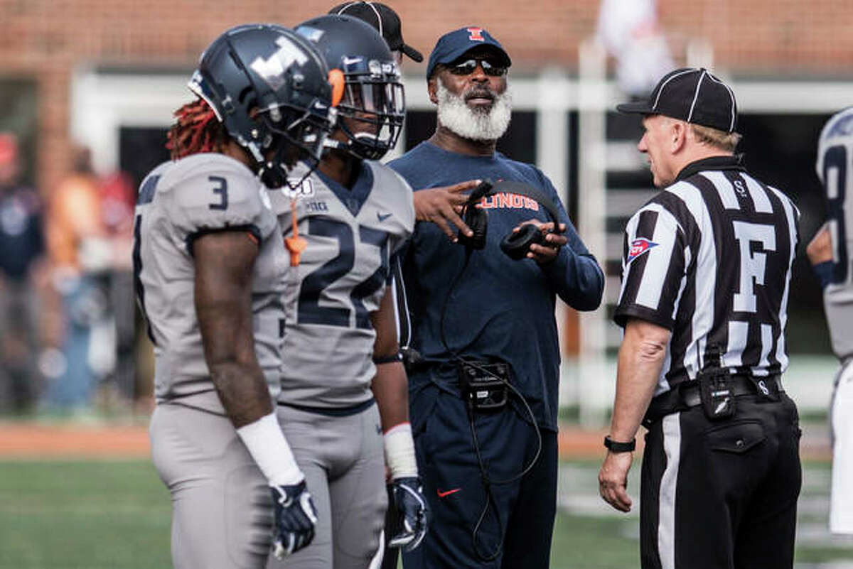 Illinois coach Lovie Smith speaks with an official during a review in the second half of Saturday's win over Wisconsin in Champaign.