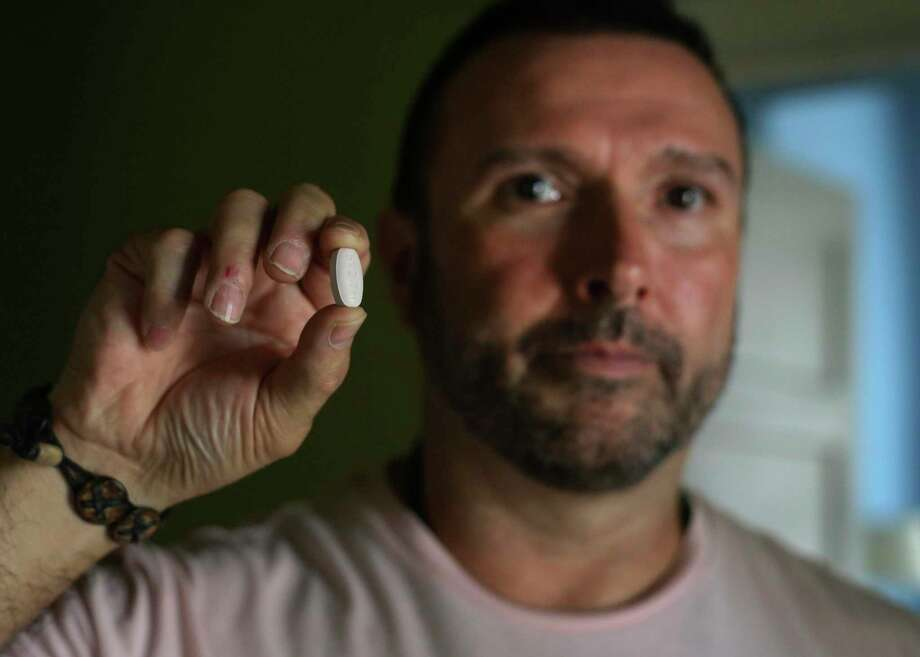 Greg Casillas shows the medication Triumeq, which he takes daily for HIV. For various reasons, he was reluctant to go on medication for HIV for 17 years. He started taking the pill in 2017. Photo: Kin Man Hui / ©2019 San Antonio Express-News