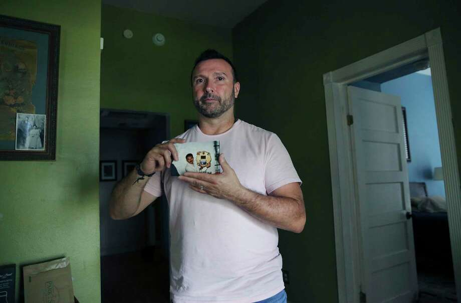 Greg Casillas holds a photograph of his brother, Paul Casillas. Greg Casillas has been HIV positive for almost 20 years and watched his brother and his brother's partner both die from AIDS. Photo: Kin Man Hui / ©2019 San Antonio Express-News