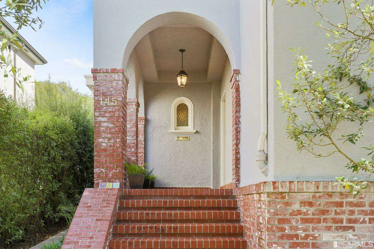 The brick and stucco 1915 home sits back from the street.