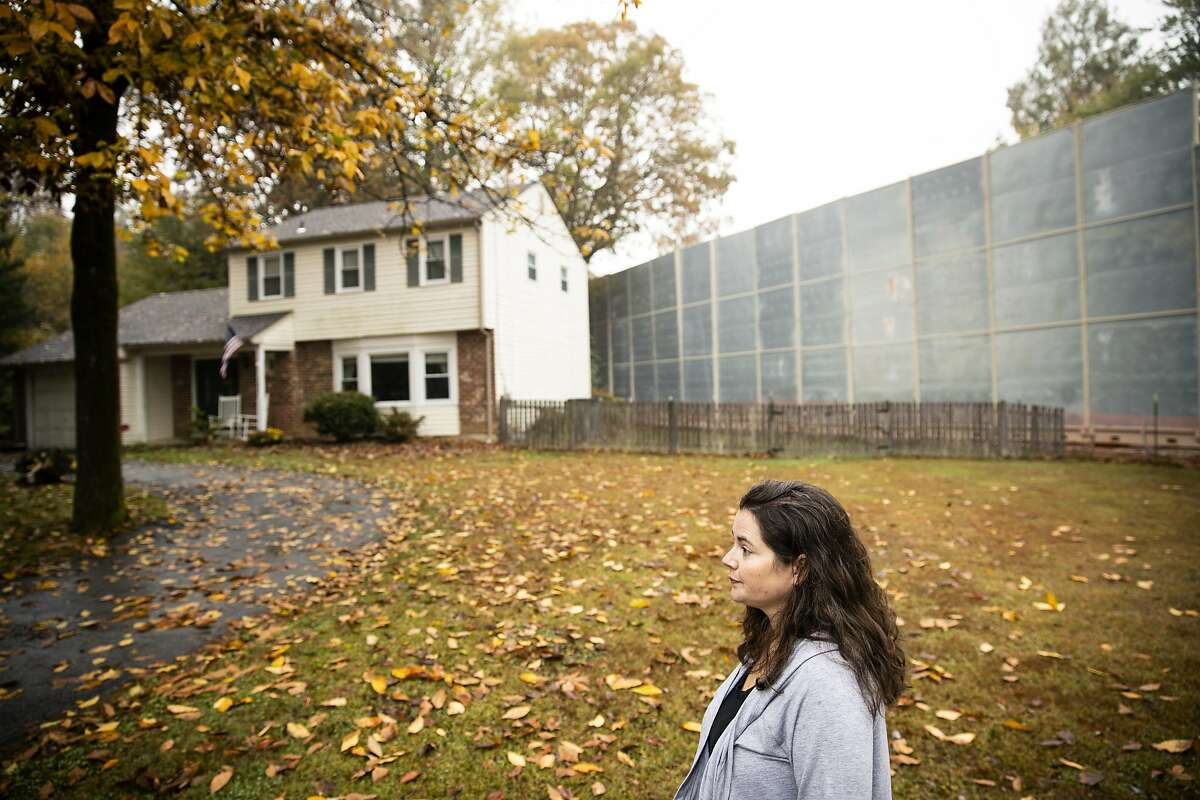 """In this Tuesday, Oct. 22, 2019 photo, Carrie Gross walks past a construction barrier shielding the Mariner East pipeline near a home during an interview with The Associated Press in Exton, Pa. The pipeline route traverses those suburbs, close to schools, ballfields and senior care facilities. """"It's absolutely traumatic and I don't say that to exaggerate or cry wolf,"""" said Gross, referring to the project that runs through backyards in her middle-class Philadelphia suburb of Uwchlan Township. """"It's devastated my neighborhood."""" (AP Photo/Matt Rourke)"""