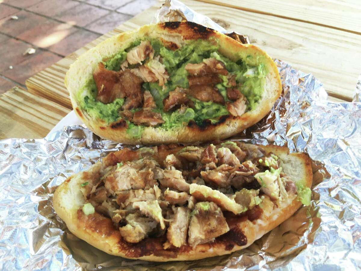 """A pork belly torta served """"moreliana"""" style with guacamole, beans and cheese at Carnitas Don Raúl."""
