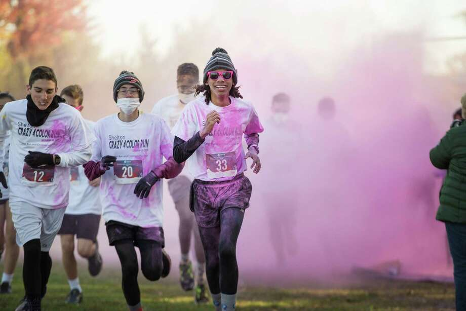Owen Corbit, Jake Daxner and Brandon Fulton of SHS Crosscountry team run at Shelton High School's Crazy 4 Color 5k run on Saturday. Photo: Bryan Haeffele / Hearst Connecticut Media / Hearst Connecticut Media