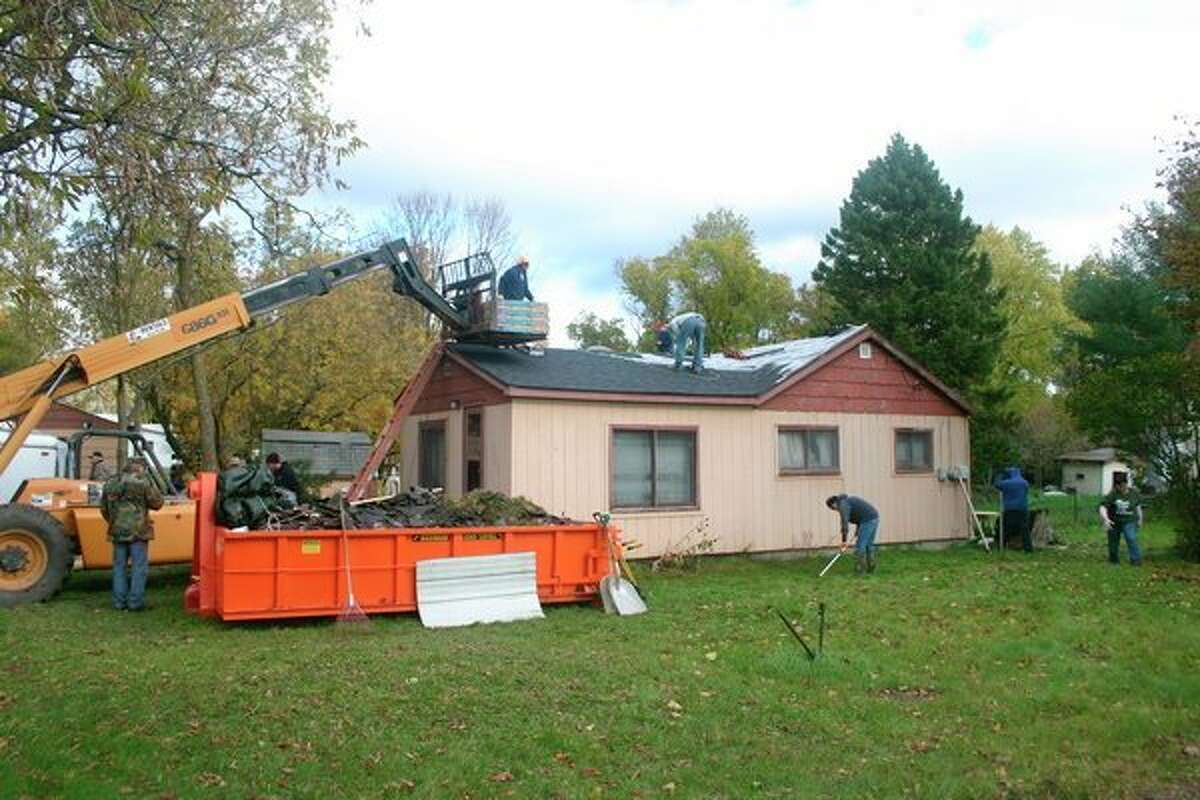 Volunteers, with the help of The Home Depot Foundation, replaced veteran John Clark's roof on Wednesday, Oct. 23. What would normally take about three days was completed in one day. (Herald Review photo/Cathie Crew)