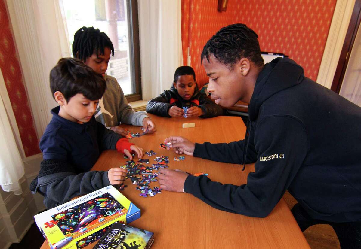 Volunteer Michael Langston helps Jeremiah Romero, 9, with a puzzle during the after-school program at the Sterling House in Stratford, Conn., on Friday, Apr. 5, 2019. Now in its third year, the program enables children from pre-school to sixth grade spend after-school hours taking enrichment classes like music, art and even yoga. Over 40 kids come each day from all but two of Stratford's schools. For more information about this or any other program call (203) 378-2606.