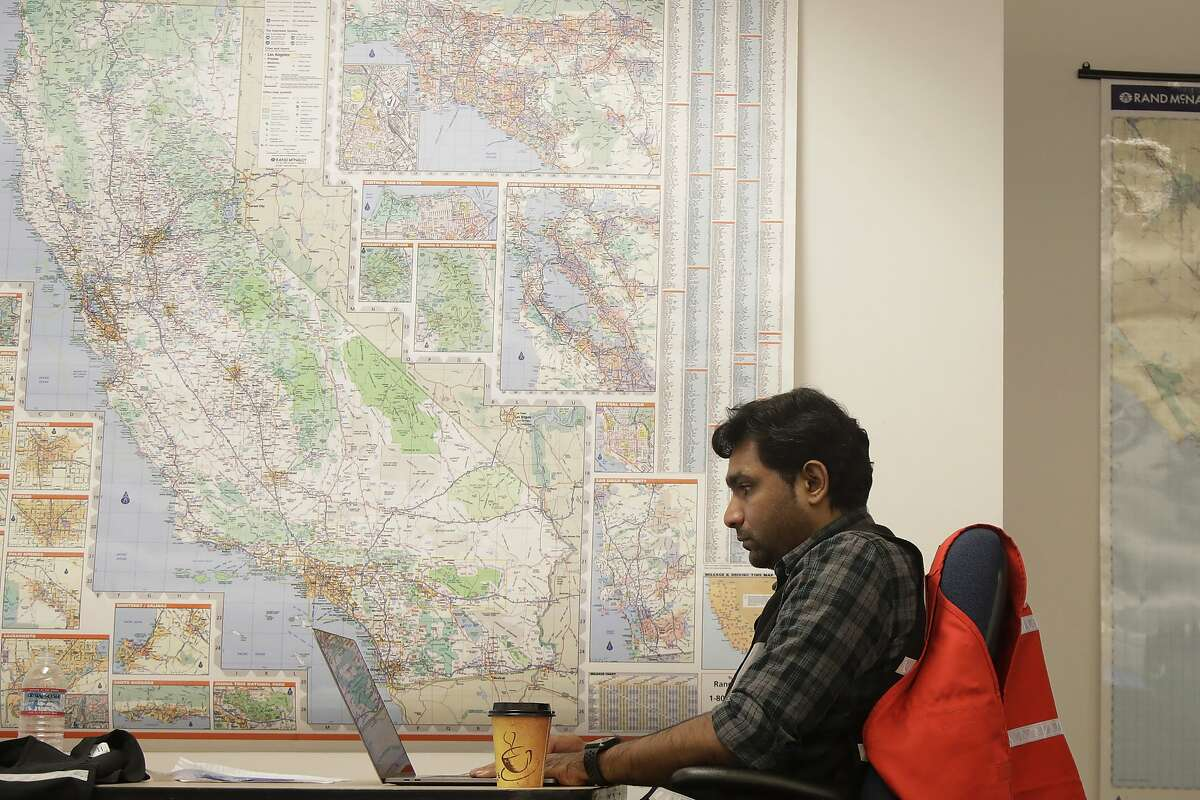 """FILE - In this Oct. 10, 2019, file photo, Senior program analyst Siva Jasti works next to a map of California in the Pacific Gas & Electric (PG&E) Emergency Operations Center in San Francisco. The California Senate will investigate a California utility's process for cutting off power to more than 2 million people to prevent wildfires. In a memo to the Senate Democratic Caucus on Thursday, Oct. 17, 2019, Senate President Pro Tempore Toni Atkins asked the Senate Energy, Utilities, and Communications Committee to """"begin investigating and reviewing options to address the serious deficiencies"""" with PG&E's current process of shutting off power to prevent wildfires. (AP Photo/Jeff Chiu, File)"""
