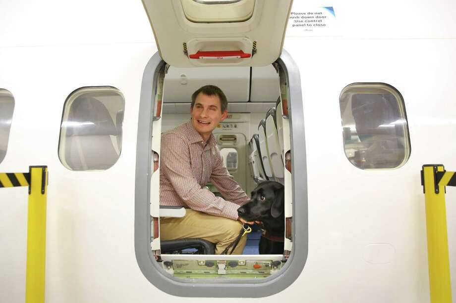 "Community outreach specialist for Guide Dogs for the Blind Jake Koch looks out the emergency exit door with his guide dog Fourly after practicing opening the door during a training event hosted by Guide Dogs for the Blind and Alaska Airlines where guide dogs, puppies-in-training and people with disabilities, including visually impaired, hearing impaired and those reliant on wheelchairs, were able to explore mock airplanes and learn various safety measures in a controlled environment, Monday, Oct. 21, 2019 at the Alaska Airlines Flight Operations Building. ""This sort of thing is helpful because when you can't see, it's hard to conceptualize flying. Something like this where you can actually feel everything increases safety and helps make it less mystical. It helps people feel more comfortable with flying,"" Koch said who has limited vision. Photo: Genna Martin, Seattlepi.com / GENNA MARTIN"