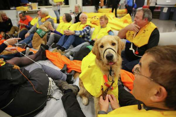 Dog and human attendees wear uninflated life vests and practice sitting in an inflatable airplane raft that would be used in an emergency situation during a training event hosted by Guide Dogs for the Blind and Alaska Airlines where guide dogs, puppies-in-training and people with disabilities, including visually impaired, hearing impaired and those reliant on wheelchairs, were able to explore mock airplanes and learn various safety measures in a controlled environment, Monday, Oct. 21, 2019 at the Alaska Airlines Flight Operations Building.