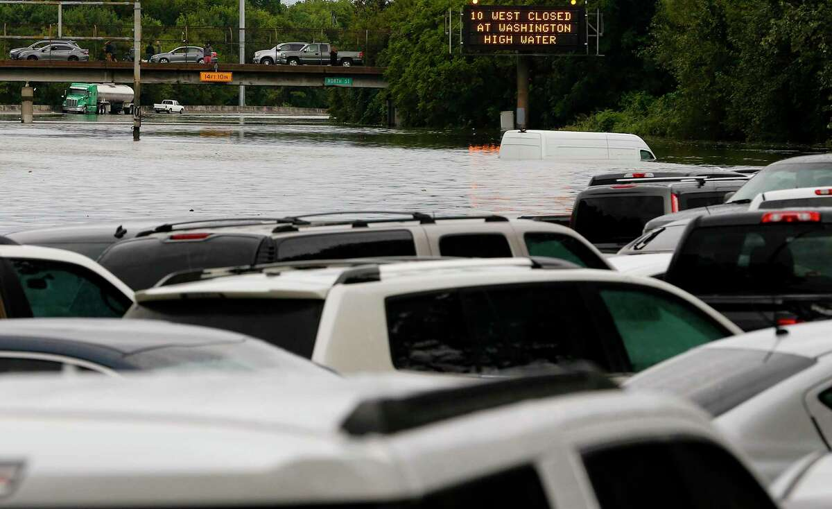 A highway sign warning of high water faces abandoned cars and trucks along southbound Interstate 45 near Main Street following Tropcial Depression Imelda on Sept. 19, 2019.