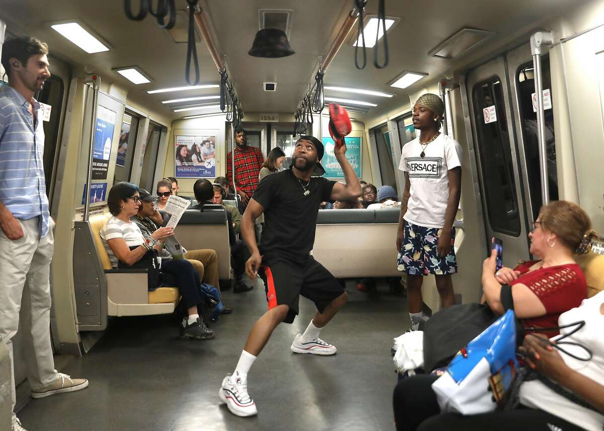 Demetrius J (middle) performs on the BART train heading to San Francisco from the 12th St. Oakland station seen on Wednesday, Oct. 23, 2019, in Oakland, Calif.