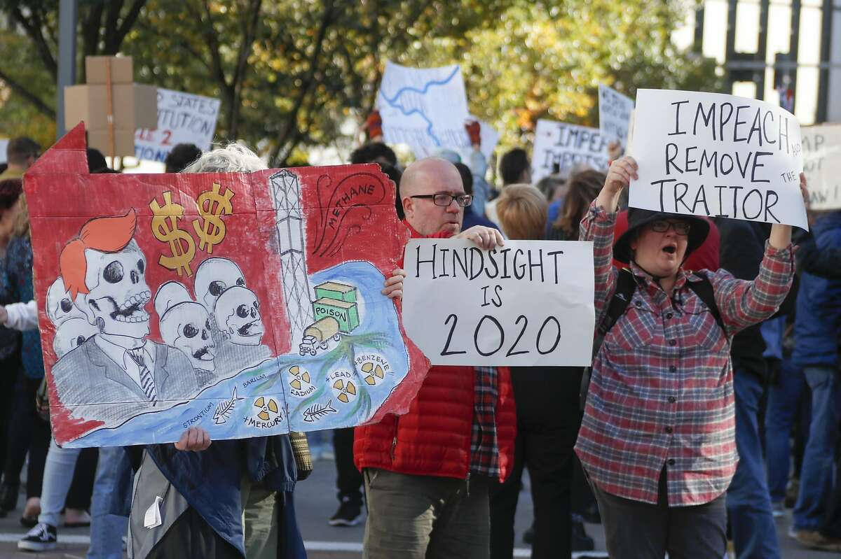 Protestors hold signs opposing fracking and the President as they rally outside the convention center where President Donald Trump was speaking at the Shale Insight Conference, Wednesday, Oct. 23, 2019, in Pittsburgh. (AP Photo/Keith Srakocic)