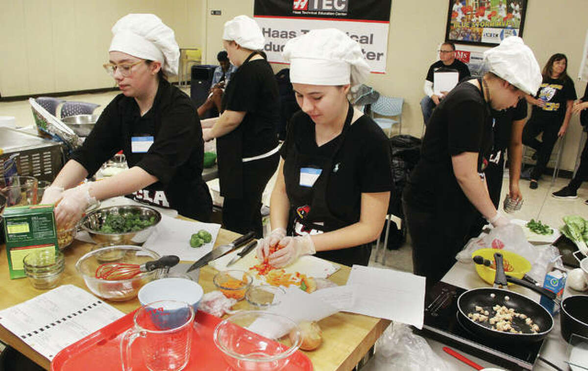 Culinary students from Alton High School work at multiple tasks during the Fourth Annual Platinum Chef Team Competition Wednesday. Students from 10 different high schools prepared an appetizer, salad/dressing, entrée and dessert at the competition, held at Southwestern Illinois College-Sam Wolf Granite City Campus.