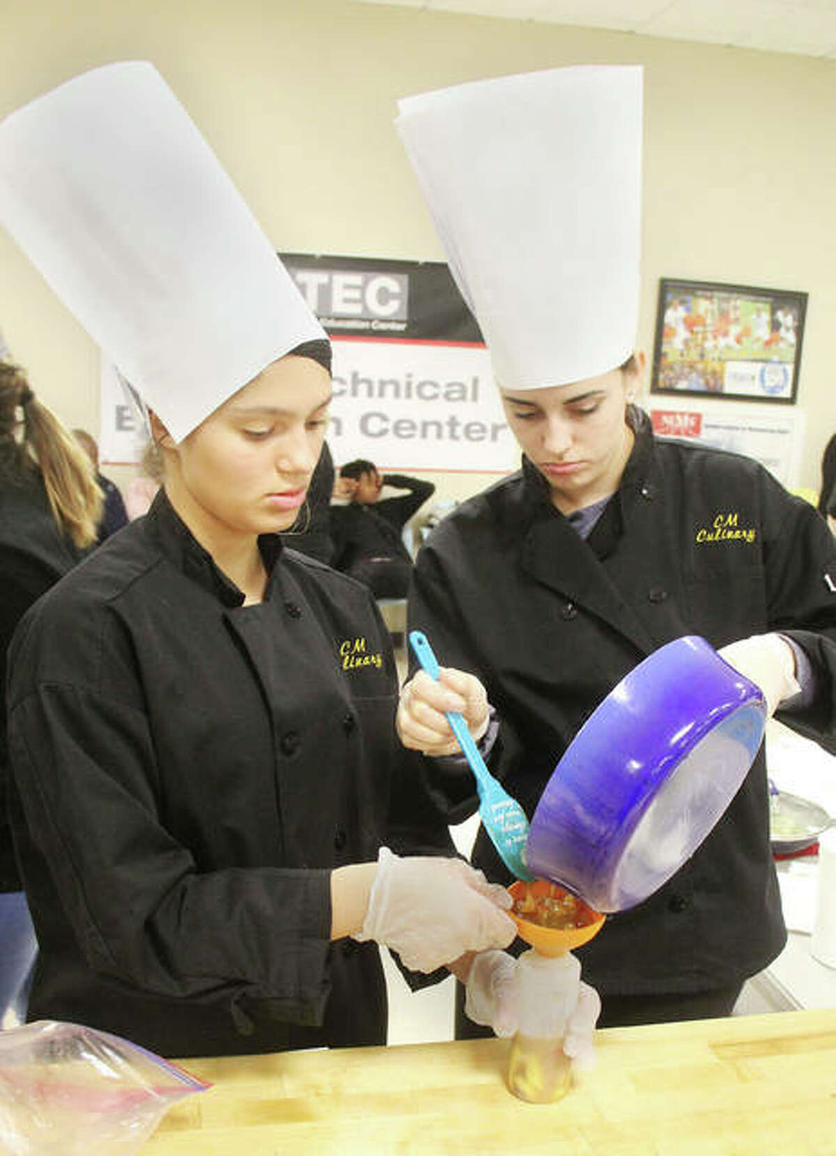 Azia Ray, left, and Anna Hall, culinary students from Civic Memorial High School, prepare a sauce during the Fourth Annual Platinum Chef Team Competition Wednesday. Students from 10 different high schools prepared an appetizer, salad/dressing, entrée and dessert at the competition, held at Southwestern Illinois College-Sam Wolf Granite City Campus.