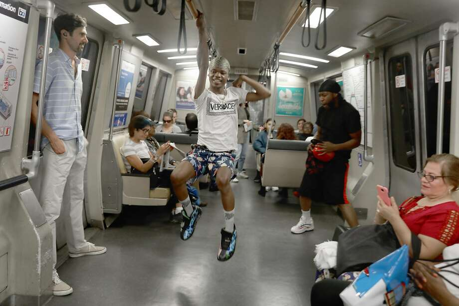 Scoot Tha Dancing (middle) performs on the BART train heading to San Francisco from the 12th St. Oakland station seen on Wednesday, Oct. 23, 2019, in Oakland, Calif. BART directors are arguing over whether to ban entertainment for solicitation, like Scoot, and panhandling within the stations. Photo: Liz Hafalia / The Chronicle