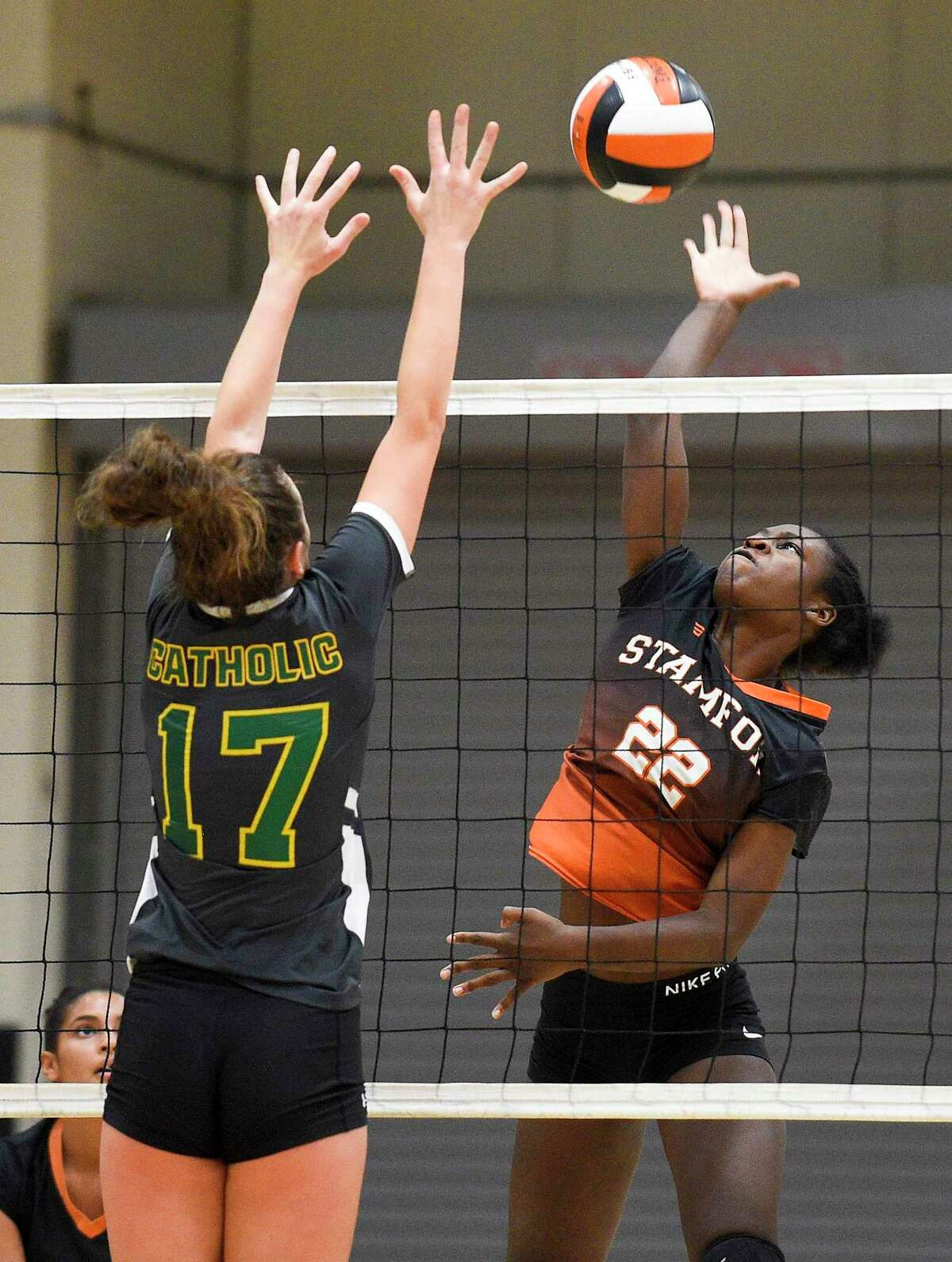 Stamford's Widline Thomas (22) taps the ball past Trinity Catholic's Valeria Barbaglio (17) during a girls volleyball match in Stamford on Oct. 23, 2019. Stamford went on to sweep Trinity Catholic in three sets 25-19, 30-28, 25-8.