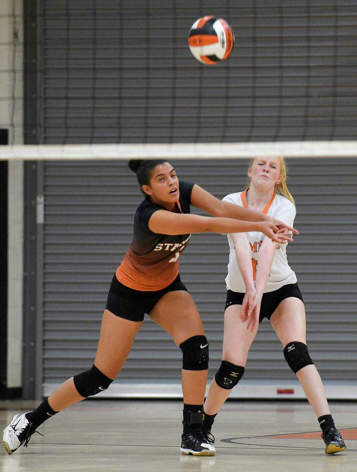 Stamford's Liani Mercado (3) and Morgan Yacavone (33) get under a service from Trinity Catholic during a girls volleyball match in Stamford on Oct. 23, 2019. Stamford went on to sweep Trinity Catholic in three sets 25-19, 30-28, 25-8.