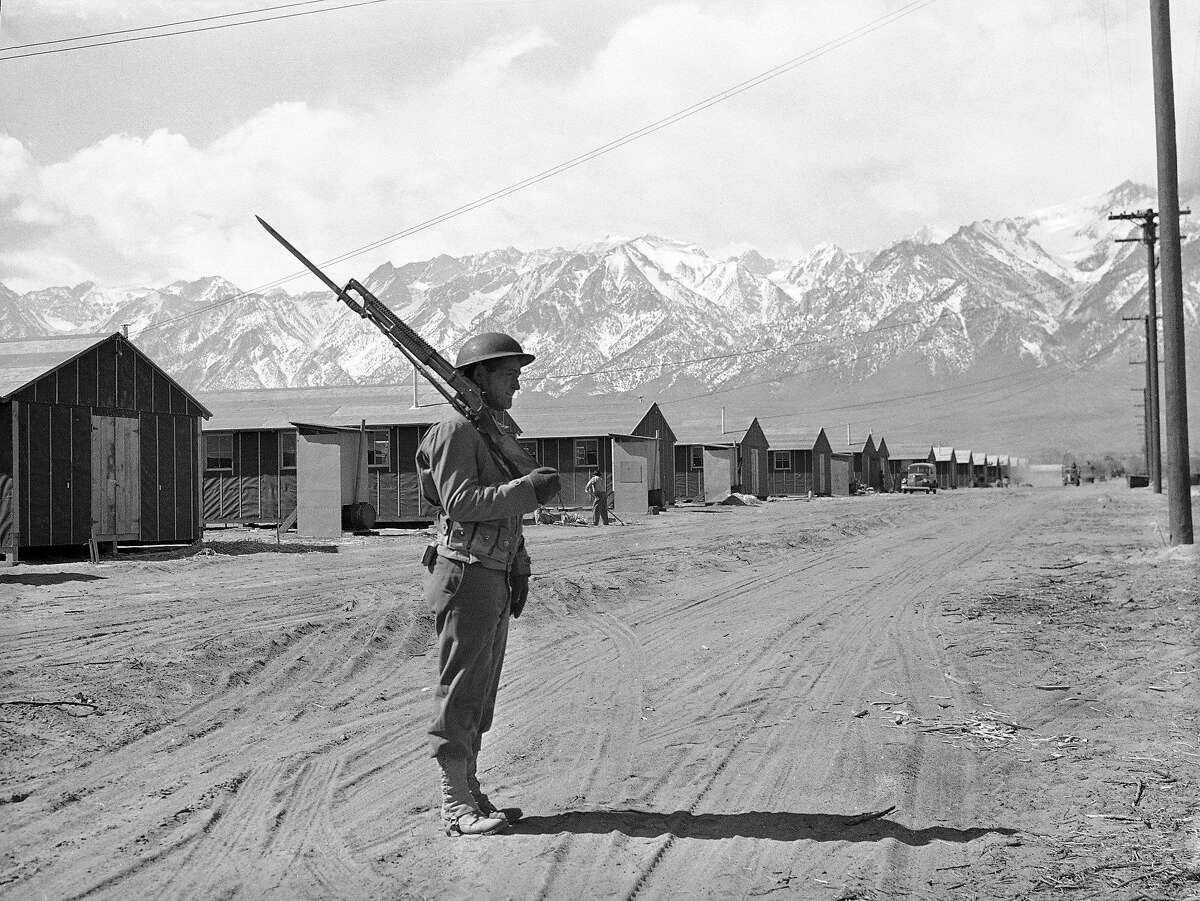 File - In this May 23, 1943, file photo, an American soldier guards a Japanese internment camp at Manzanar, Calif. A human skeleton retrieved from California's second-highest mountain, Mount Williamson, in October 2019, may be the remains of a Japanese-American man who died in 1945 as part of a fishing party from the Manzanar internment camp. The Inyo County Sheriff's Department says that is among the possibilities being investigated after the bones were discovered Oct. 7 by two hikers. (AP Photo/File)