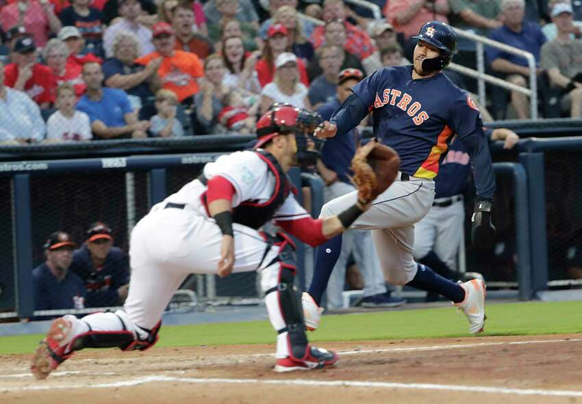 FILE - In this March 12, 2019, file photo, Houston Astros' Carlos Correa heads for home as Washington Nationals catcher Yan Gomes waits for the ball during the third inning of a spring training baseball game in West Palm Beach, Fla. Correa was out. The Astros and Nationals began the year by sharing their Ballpark of the Palm Beaches spring training home. More than 200 days after breaking camp, they'll end the year on the same field with much more at stake. Seven spring training sites currently host two teams, including Camelback Ranch, home of the Los Angeles Dodgers and Chicago White Sox. (AP Photo/Brynn Anderson, File)