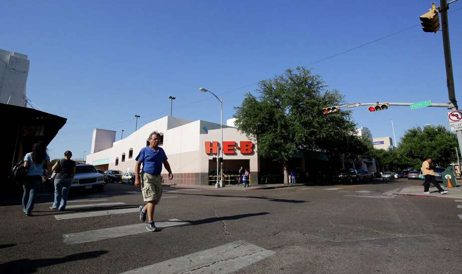 Pedestrians cross the street in front of Laredo's downtown H-E-B, 1002 Farragut St., Friday. H-E-B announced Friday that the company will be closing this store June 26. Photo: Victor Strife