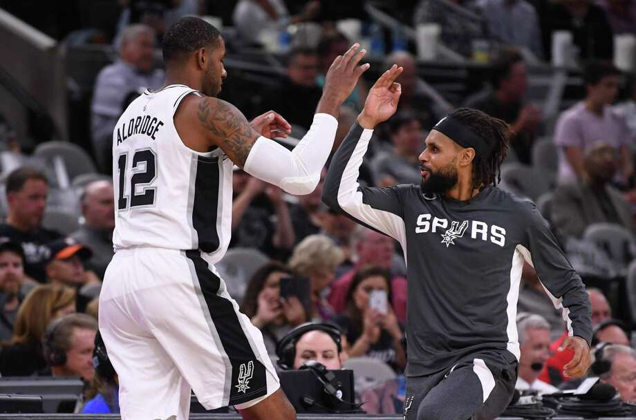 San Antonio Spurs forward LaMarcus Aldridge is greeted by teammate Patty Mills before the tipoff of the team's season opener against the New York Knicks in the AT&T Center on Wednesday, Oct. 23, 2019. Photo: Billy Calzada / Staff Photographer / San Antonio Express-News
