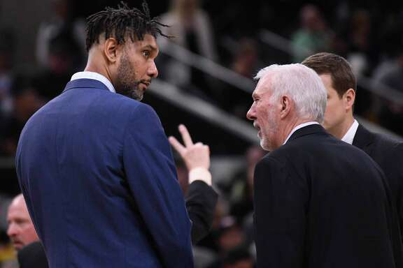 San Antonio Spurs assistant coach Tim Duncan, left, speaks with head coach Gregg Popovich during a timeout in their game against the New York Knicks in the AT&T Center on Wednesday, Oct. 23, 2019.