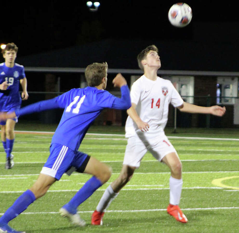 Alton's Evan Dugger (14) heads the ball away from Ben Terweip of Quincy during Wednesday night's Class 3A regional semifinal game in Edwardsville. The Redbirds won 2-1 and will face rival Edwardsville for the regional championship at 4 p.m. Friday. Photo: Pete Hayes | The Telegraph