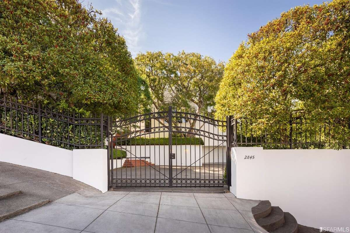 The 1939 home sits behind a gate and has a seven-car motor court.