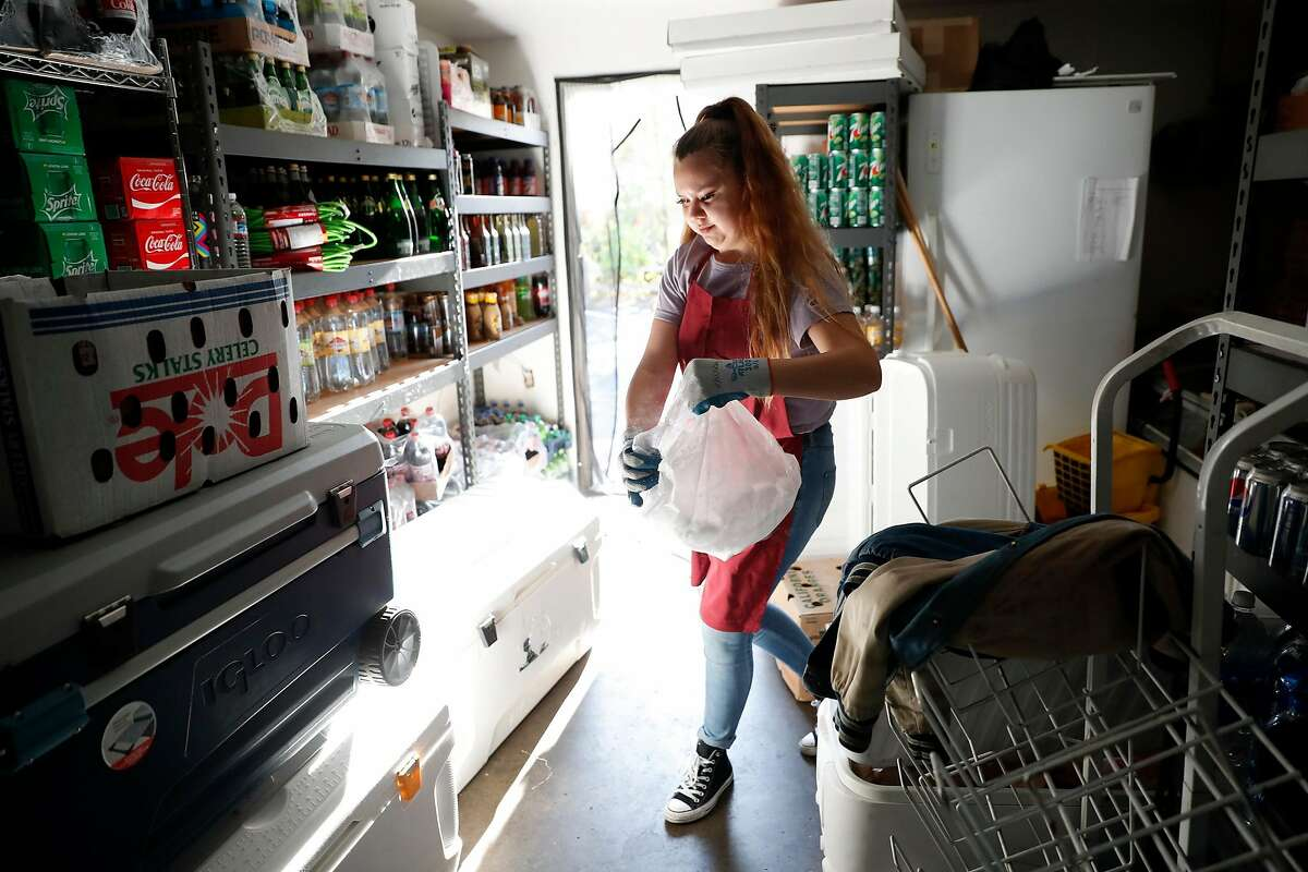 Oakmont Village Market employee Destiny Rivera carries a bag of dry ice to place in a cooler during PG&E power shut-off in Santa Rosa, Calif., on Wednesday, October 23, 2019.