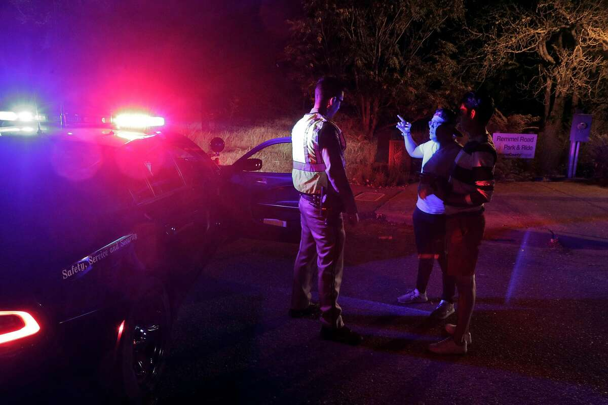 Manuel Arzate, center, and Alexis Avalos, right, ask a CHP officer to pass to help evacuate Manuel's parents on a farm his father manages as the Kincade Fire burns outside Geyserville, Calif., on Thursday, October 24, 2019.