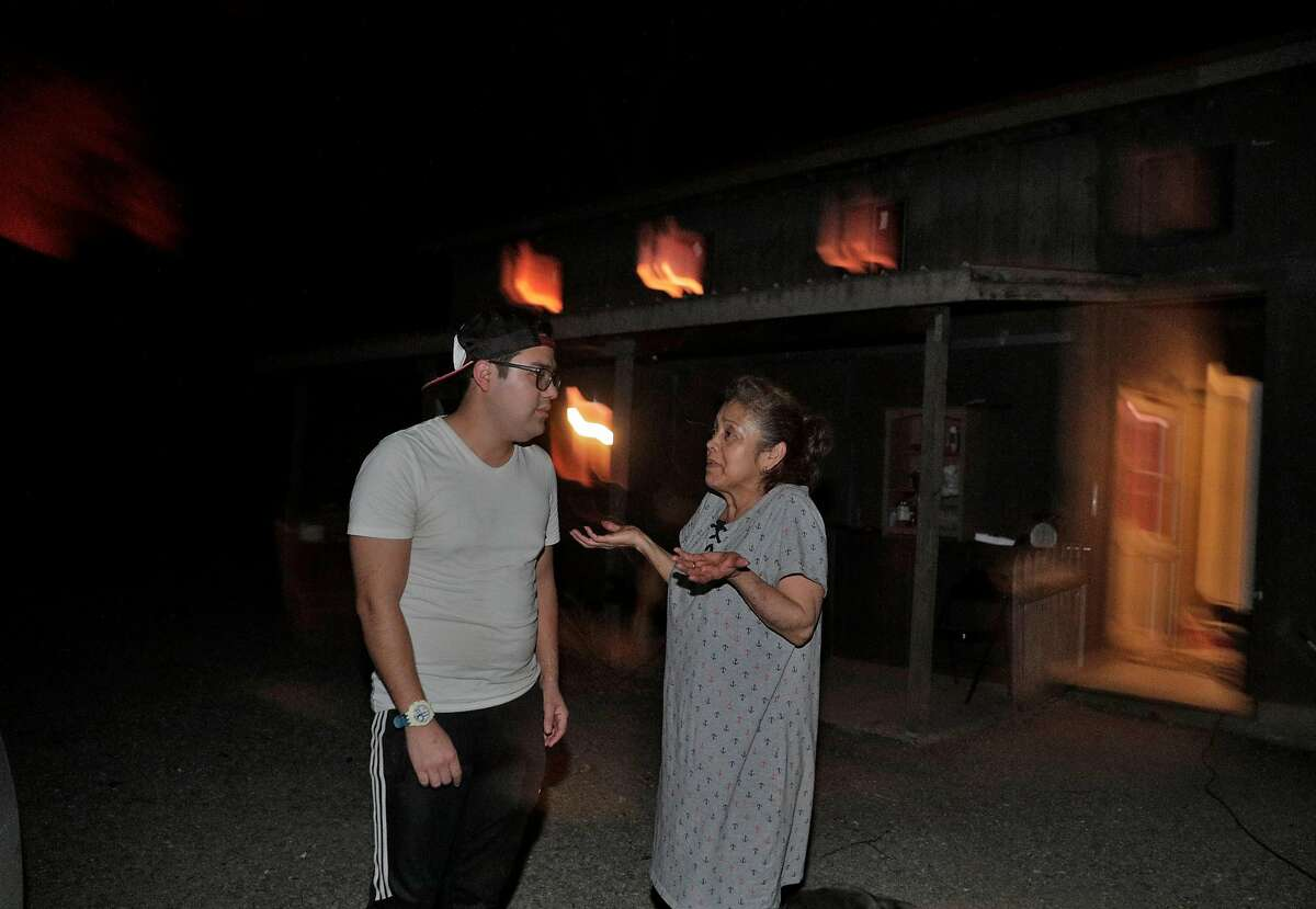 Maria Pelayo says she doesn't want to evacuate until the morning as her son, Manuel Arzate tries to convince her to lieave as the Kincade Fire burns outside Geyserville, Calif., on Thursday, October 24, 2019.