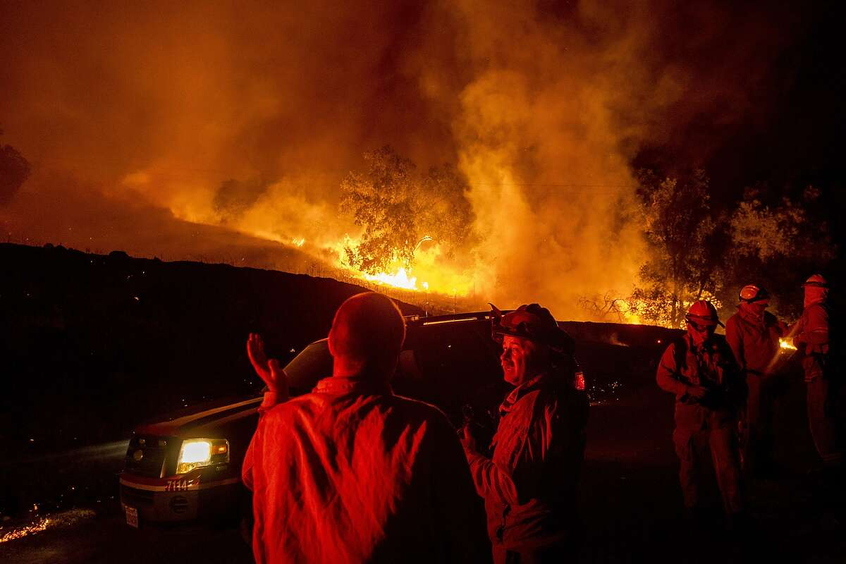 Firefighters confer while battling the Kincade Fire near Geyserville, Calif., on Thursday, Oct. 24, 2019. Portions of Northern California remain in the dark after Pacific Gas & Electric Co. cut power to prevent wildfires from sparking during dry and windy conditions. (AP Photo/Noah Berger)
