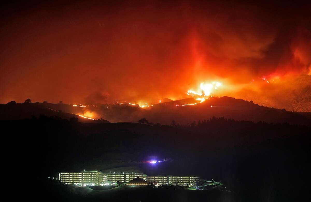 The River Rock Casino sits below a ridge line on fire as the Kincade Fire burns outside Geyserville, Calif., on Thursday, October 24, 2019.