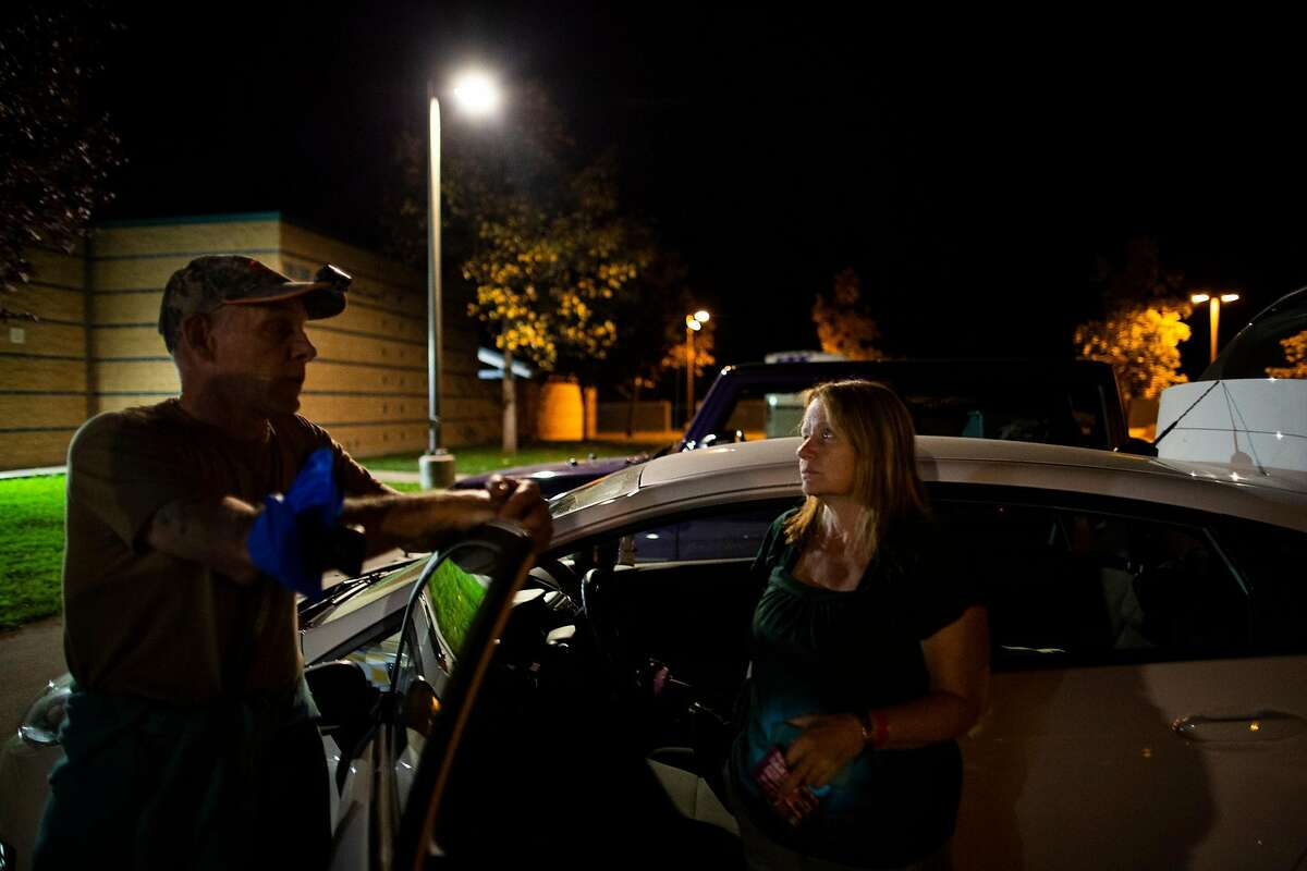 Matt and Mary Ceglarski-Sherwi (who rent a home in Geyserville) in front of their car, at the evacuation center at Windsor High School, Windsor, California, October 24th, 2019. Mary has bad asthma, the smoke woke her at 2:30am, much as it did during the Tubbs fire where their home bunt down.