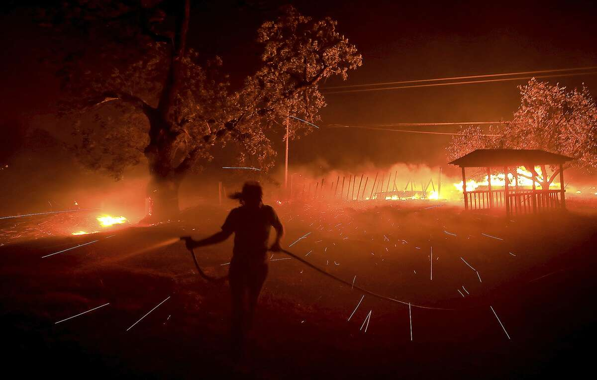 Susi Weaver, the manger for the Hawkeye Ranch in the Mayacamas Mountains above Geyserville, Calif., sprays down the dry brush as the Kincade fire delivers firebrands across the property, Thursday, Oct. 24, 2019.