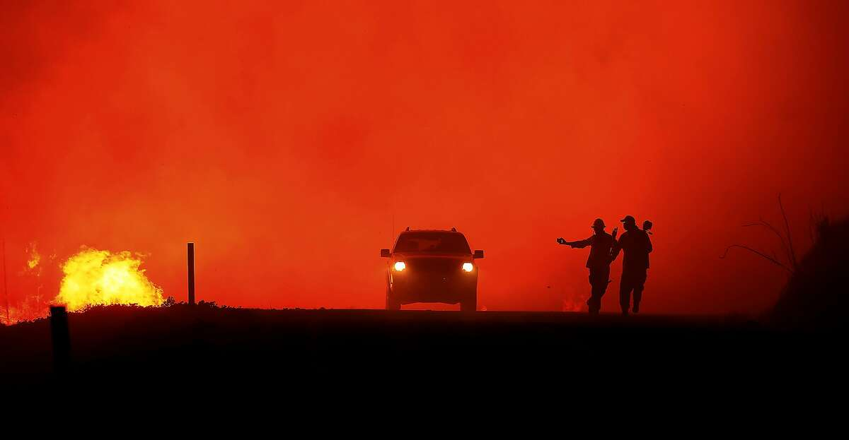 Photographers documenting the Kincade fire in the Geysers run as the fire approaches Geysers Road, Thursday, Oct. 24, 2019, in Sonoma County, Calif. (Kent Porter/The Press Democrat via AP)