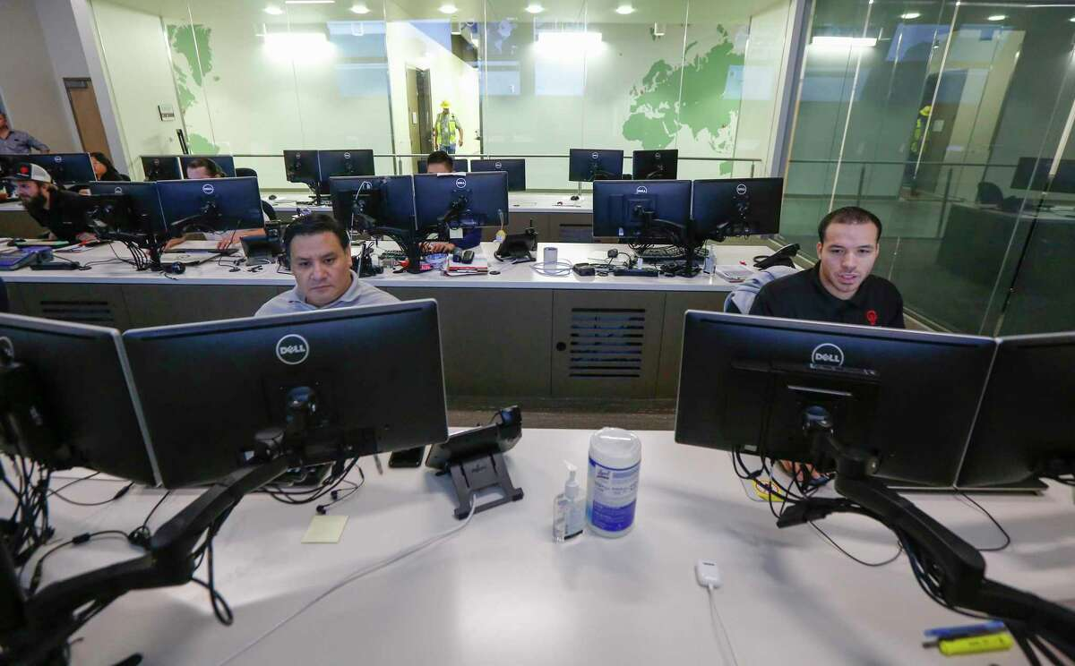 Julio Prado (left) and Marquis Newberry-Payne work in a computer operations room in Data Foundry - Houston 2 Wednesday, Oct. 23, 2019, in Houston.