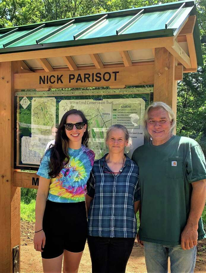 Nick Parisot's sister Michelle Parisot, his mother Kate Throckmorton, and his father Rick Parisot at the dedication this summer of a kiosk at the head of a trail blazed in Nick's memory. Photo: Contributed Photo / Wilton Conservation Land Trust / Wilton Bulletin Contributed
